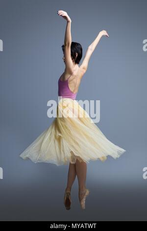 ballerina is dancing in the studio on a gray background  - Stock Photo