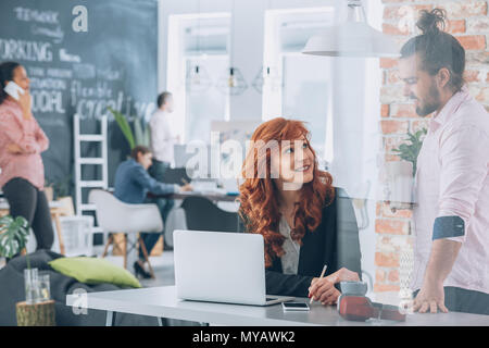 Young woman flirting with coworker during work