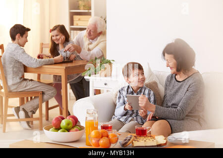 Happy grandchildren visiting their grandparents and spending free time with them - Stock Photo