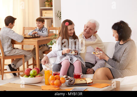 Happy family eating a cake in a living room - Stock Photo