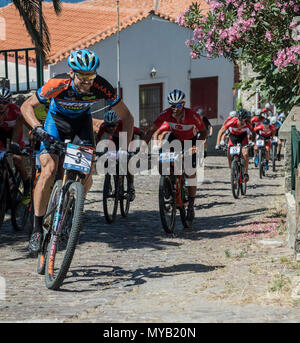 The initial pack of cyclists on the first lap of an international mountain bike race in the Greek village of Molyvos on the island of Lesvos - Stock Photo