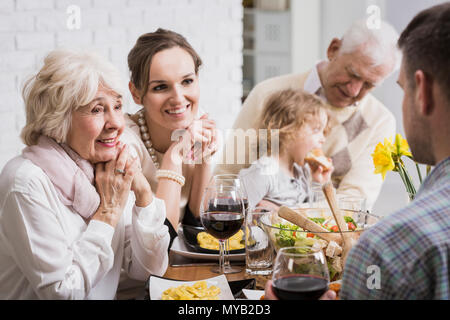 Happy family sitting beside table during dinner, granddaughter sitting on grandfather's lap