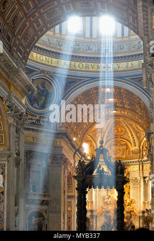 Saint Peter's Basilica, interior looking down nave with light (Crepuscular or God rays) from dome, with baldacchino (right), Vatican City, Rome, Italy - Stock Photo