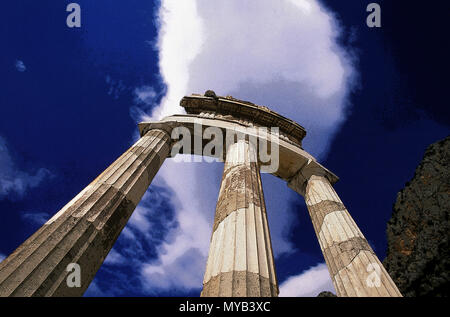 Doric Tholos at Sanctuary of Athena Pronaia (ca. 390 BCE), Delphi, looking up at entablature with cloud, by Theodoros of Phokaia, Delphi, Greece - Stock Photo