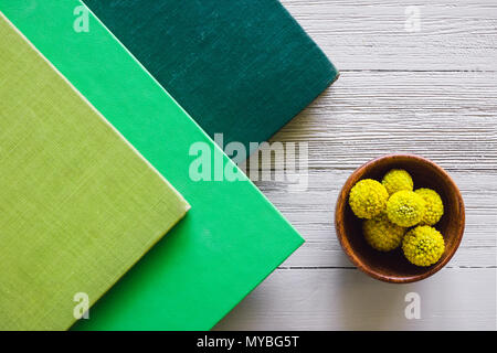Stacked Green Covered Books with Craspedia on White Table