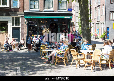 Tourists and local people enjoy the dutch cafe Hegeraad located just steps away from the Prinsengracht , Amsterdam, Netherlands - Stock Photo