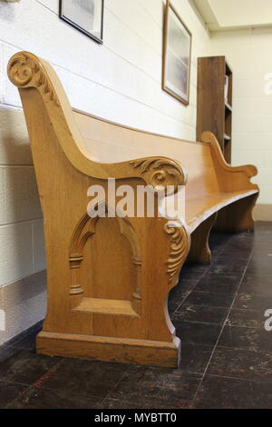 Carved wood church pew in the basement At Ebenezer Lutheran church in Chicago, Illinois. - Stock Photo