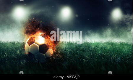 Soccer ball with fire effect on the lawn of the stadium, viewed in close-up against dark background with copy space. 3d Rendering - Stock Photo