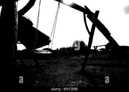 Abandoned swing in warm sunny light, in the spring season. summer - Stock Photo