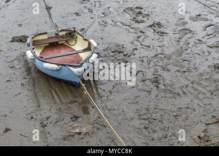 Small rowing boat beached on muddy river bank. - Stock Photo