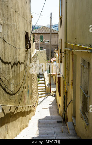 View from the top of the narrow alley, stuck between townhouses, leading down to the Vallon des Auffes, a small fishing port in Marseille, France. - Stock Photo