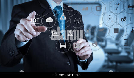 Internet of Things (IOT) technology with AR (Augmented Reality) on VR dashboard. Businessman hand pressing an imaginary button on virtual screen - Stock Photo