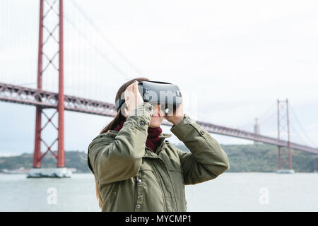 Young beautiful girl wearing virtual reality glasses. 25th of April bridge in Lisbon in the background. The concept of modern technologies and their u - Stock Photo