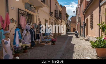Streets of Olbia old town with local clothes shop displaying goods outside, Sardinia - Stock Photo