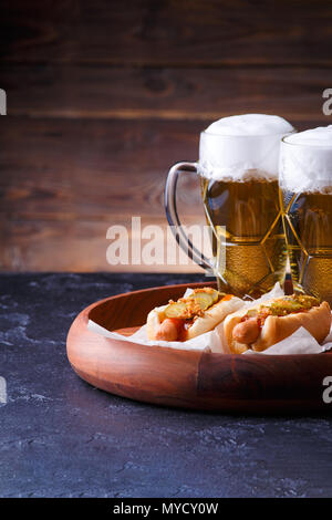 Photo of two glasses of beer and hot dogs on wooden tray - Stock Photo