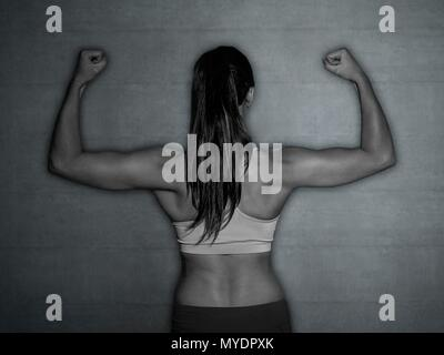 Young woman in sports top flexing muscles, rear view. - Stock Photo