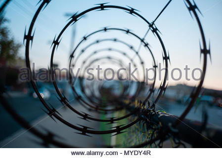 Spiraling razor wire tops a chain link fence. - Stock Photo