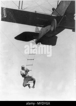 Fearless Freddie, a Hollywood stunt man, clinging to a rope ladder slung from a plane flown by A.M. Maltrup, about to drop into automobile below- automobile not shown - Stock Photo