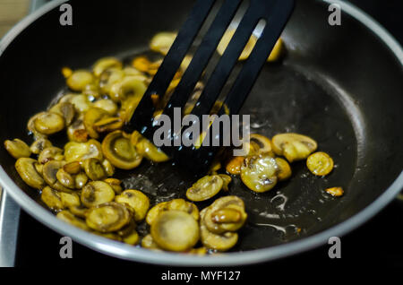 sliced mushrooms fried in butter in a pan, vegetarian dish, healthy snack - Stock Photo