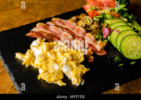 scrambled eggs with bacon, mushrooms served with salad, tomato and cucumber, breakfast set - Stock Photo