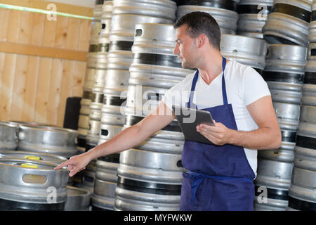 male brewer with a metal beer barrel - Stock Photo