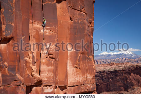 A male rock climber in colorful clothing ascends a crack climb known as Chasin skirt above the Colorado River in front of the La Sal mountains. - Stock Photo