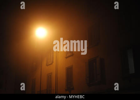 Misty and spooky street scene at night in the city. - Stock Photo