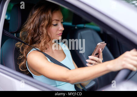 Woman driving whilst using mobile phone - Stock Photo
