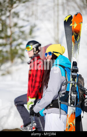 Image of sports men and women with mountain skis walking on snow hill - Stock Photo