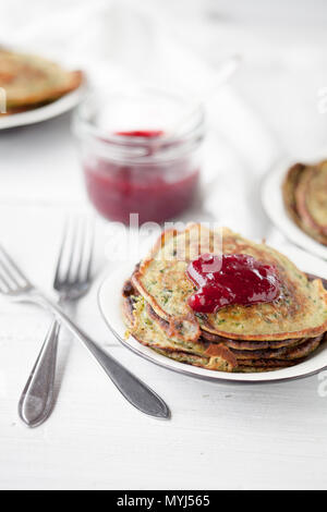 Homemade spinach pancakes with lingonberry jam - Stock Photo