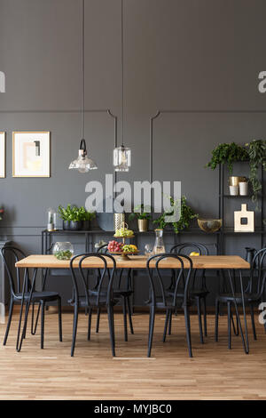 Black chairs at wooden table in grey dining room interior with lamps and plants. Real photo