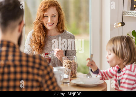 Young family eating breakfast together in a living room with big window - Stock Photo
