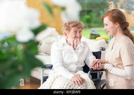 Smiling senior woman in a wheelchair and friendly nurse - Stock Photo