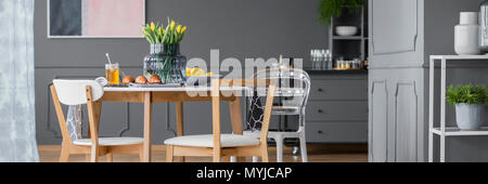 Plastic chair at a wooden table with yellow flowers in modern dining room interior with grey cabinet - Stock Photo