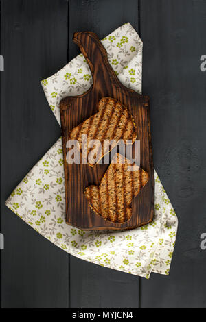 Toast with avocado made from corn bread on the grill for breakfast. White napkin with spikes and a black wooden background. Copy space, flat lay. - Stock Photo