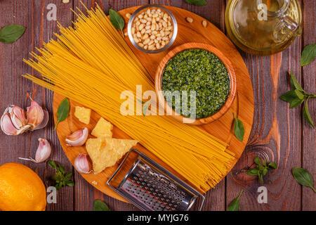 Green basil pesto - italian recipe ingredients on wooden table, top view. - Stock Photo