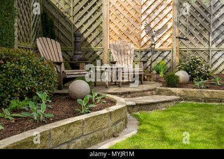 Beautiful, landscaped, private garden close-up with contemporary design, border plants, patio seating & ornamental features - Yorkshire, England, UK. - Stock Photo