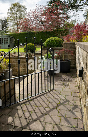 View through open gate to beautiful, landscaped, private garden with contemporary design, shrubs, box balls, path & neat lawn - Yorkshire, England, UK - Stock Photo