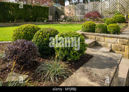 Corner of beautiful, landscaped, private garden with contemporary design, border plants, patio seating, lawn & terracing - Yorkshire, England, UK. - Stock Photo