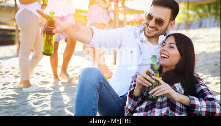 Happy young couple drinking beer and having fun at the beach