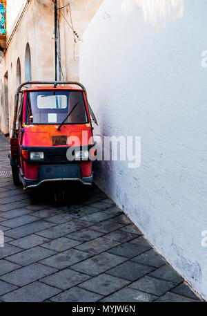 Tiny truck / car in Italy parked on the side of a road. Frontal view - Stock Photo