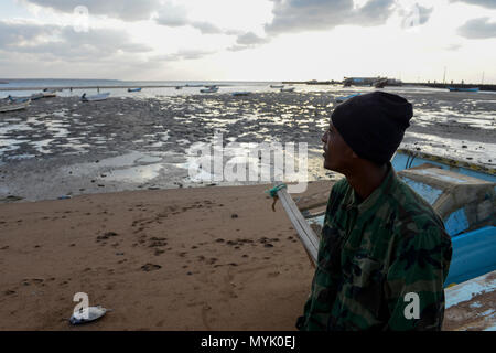 DJIBOUTI , Obock, from here ethiopian migrants try to cross bab el mandeb, red sea, gulf of aden by smuggler boats to Yemen to continue the journey to Saudi Arabia or Europe, ethiopian migrant looking to the sea / DSCHIBUTI, Obock, Meerenge Bab el Mandeb, mit Hilfe von Schleppern versuchen aethiopische Migranten hier nach Jemen ueberzusetzen, um weiter nach Saudi Arabien oder Europa zu gelangen - Stock Photo