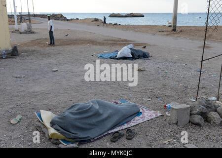 DJIBOUTI , Obock, from here ethiopian migrants try to cross bab el mandeb, red sea, gulf of aden by smuggler boats to Yemen to continue the journey to Saudi Arabia or Europe, ethiopian migrants sleeping outside at the sea / DSCHIBUTI, Obock, Meerenge Bab el Mandeb, mit Hilfe von Schleppern veruchen aethiopische Migranten hier nach Jemen ueberzusetzen, um weiter nach Saudi Arabien oder Europa zu gelangen, Fluechtlinge schlafen in der Nacht am Hafen - Stock Photo