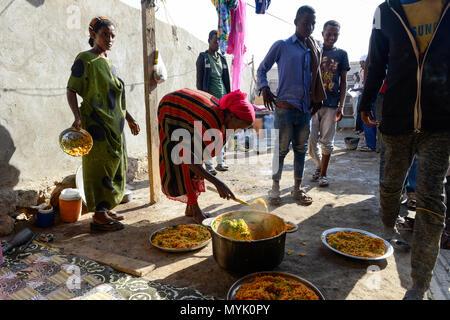 DJIBOUTI , Obock, from here ethiopian migrants try to cross bab el mandeb by boat to Yemen to go on to Saudi Arabia or Europe, the ethiopian woman Amina offers food for migrants in her kitchen / DSCHIBUTI, Obock, Meerenge Bab el Mandeb, mit Hilfe von Schleppern aethiopische Migranten versuchen hier nach Jemen ueberzusetzen, um weiter nach Saudi Arabien oder Europa zu gelangen, die Aethioperin Amina versorgt aethiopische Fluechtlinge mit einer warmen Mahlzeit in ihrer Kueche, mitte Nema Mohammed Hassan - Stock Photo
