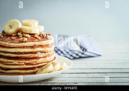 Pancakes with banana,walnut and muple syrup for a breakfast on wooden background closeup - Stock Photo