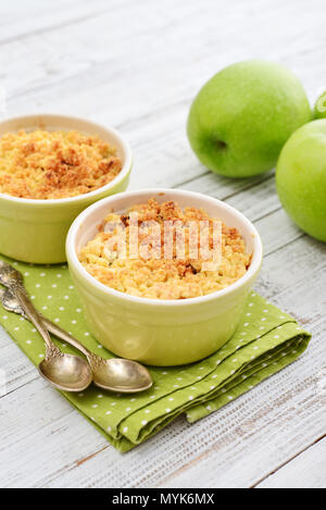 Apple crumble in small baking dish with fresh apples on wooden background - Stock Photo