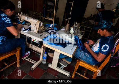 A Salvadoran seamster sews an indigo-dyed tote bag on the sewing machine in an artisanal clothing workshop in Santiago Nonualco, El Salvador. - Stock Photo