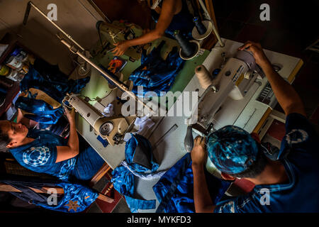 Salvadoran seamstresses sew indigo-dyed tote bags on the sewing machines in an artisanal clothing workshop in Santiago Nonualco, El Salvador. - Stock Photo