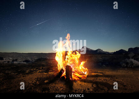 Exploring the wilderness in summer. A glowing camp fire at dusk providing comfort and light to appreciate nature, good times and the night sky full of - Stock Photo