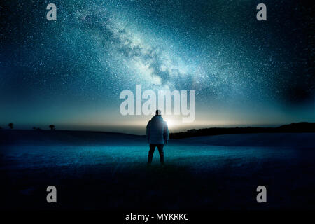 A man stands watching with wonder and amazement as the moon and milky way galaxy fill the night sky. Night time landscape. Photo composite. - Stock Photo